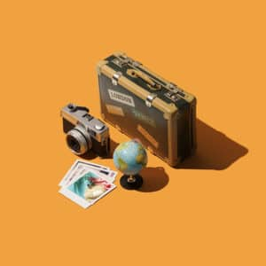 Getting ready to leave for summer vacations: vintage suitcase, globe and digital camera, travel and tourism concept